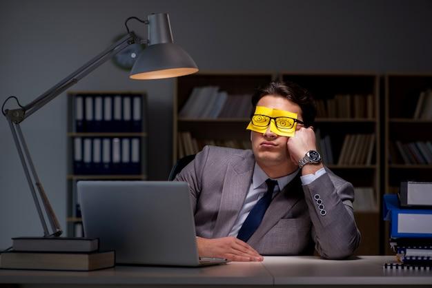 優先順位を整理するために遅く滞在するビジネスマン