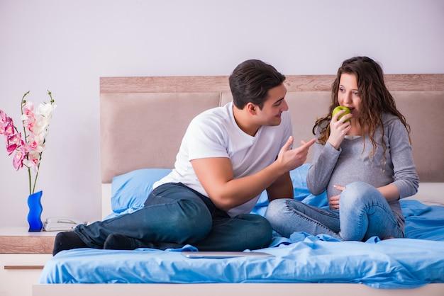 Молодая семья с беременной женой, ожидающей ребенка в постели
