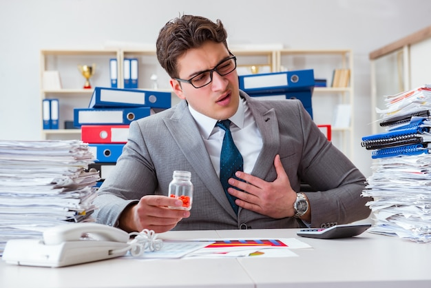 Бизнесмен, принимая таблетки, чтобы справиться со стрессом
