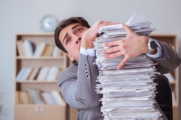 オフィスで書類で忙しいビジネスマン