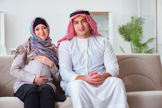 妊娠中の妻が赤ちゃんを期待して若いアラブのイスラム教徒の家族