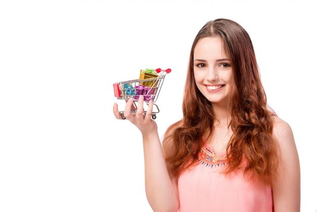 白で隔離されるショッピングカートを持つ若い女性