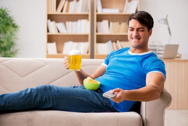 自宅でソファに座ってサッカーを見ている男