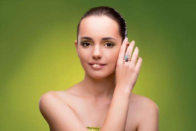 Молодая женщина в концепции красоты на зеленой стене