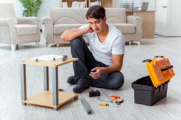 自宅で家具を組み立てる男