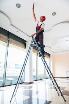 建設コンセプトの天井を塗る若い画家