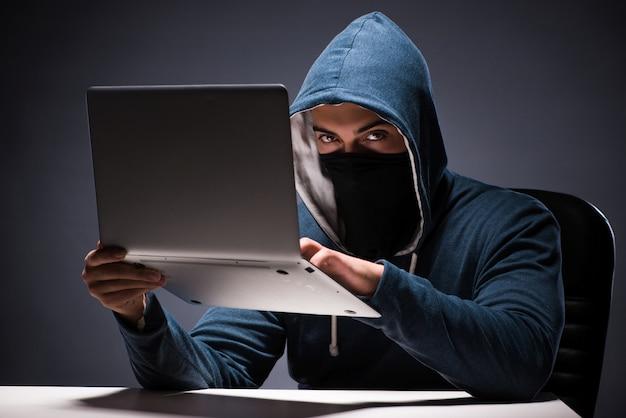 Компьютерный хакер работает в темной комнате
