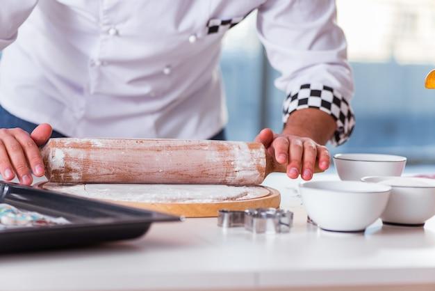 若い男が台所でクッキーを調理