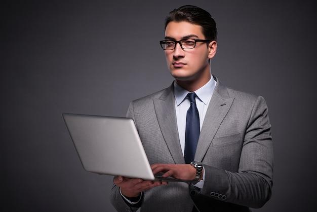 ラップトップコンピューターで作業してハンサムな実業家
