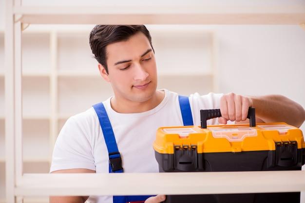本棚の組み立てを修復する労働者の男