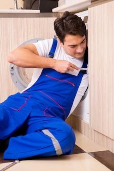Ремонтник ремонтирует стиральную машину на кухне
