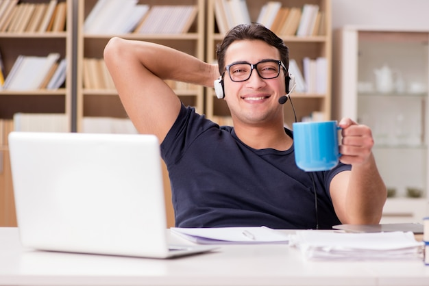 Молодой студент пьет кофе из чашки