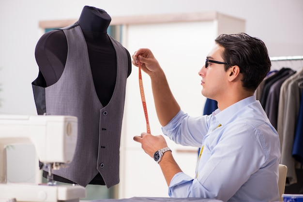 新しい服に取り組んでいる若い男のテーラー