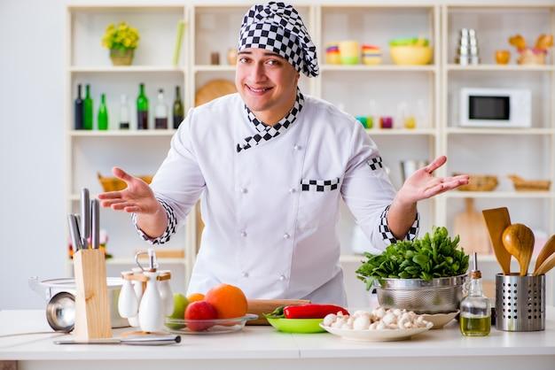 キッチンで働く若い男性料理人