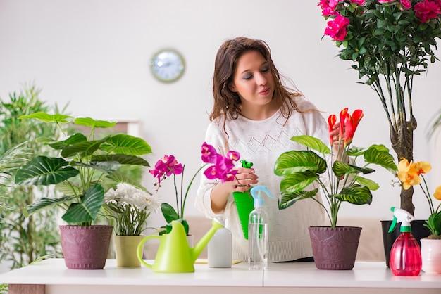Молодая женщина ухаживает за растениями в домашних условиях