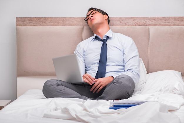 Бизнесмен работает в постели у себя дома