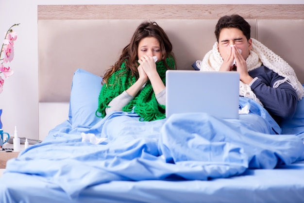 病気の妻と夫のラップトップでベッドで