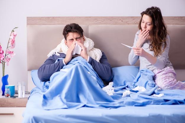 自宅のベッドで病気の夫の世話をする妻