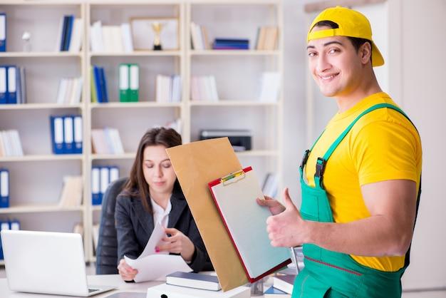 オフィスに小包を配達する郵便配達員