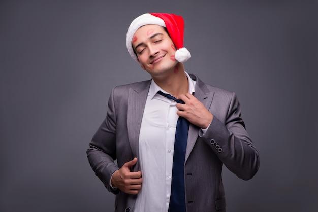 サンタの帽子とのキスで覆われた男