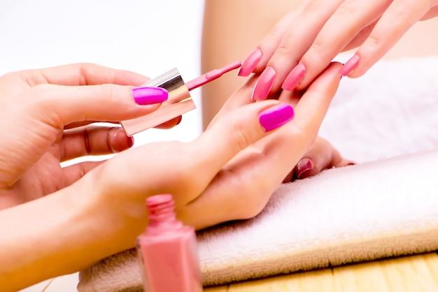 Руки женщины во время процедуры маникюра