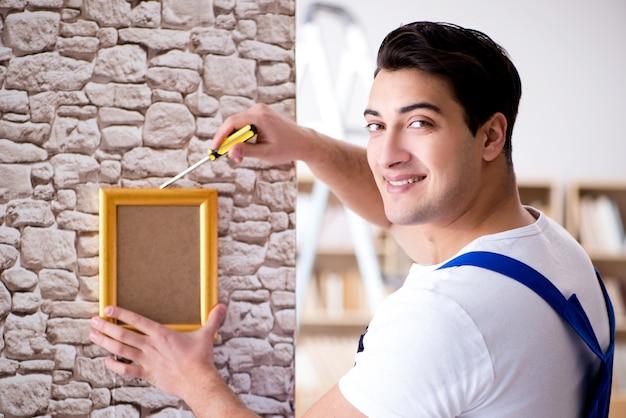 壁に額縁を置く修理工