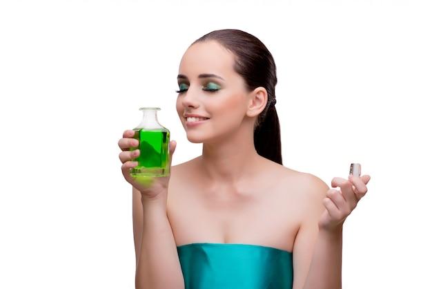 緑の香水のボトルを保持している女性