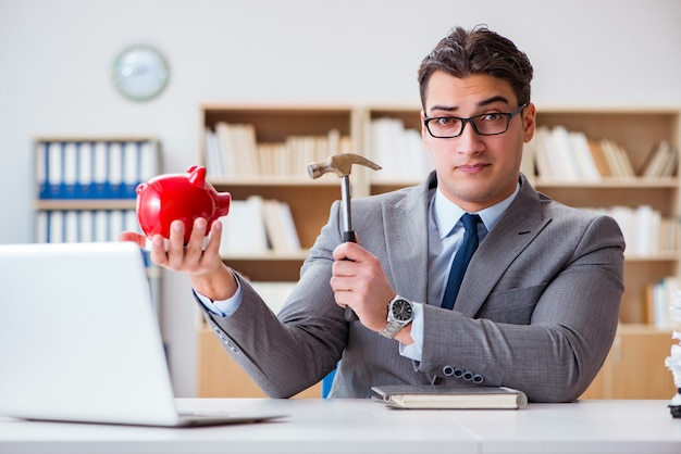 Бизнесмен ломает копилку в офисе