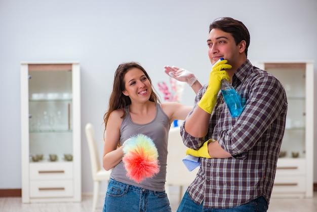 Жена и муж занимаются уборкой дома