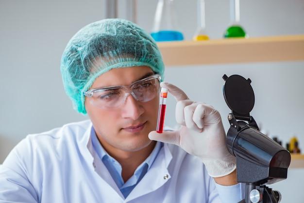Молодой доктор работая на анализе крови в больнице лаборатории