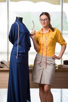 新しい服に取り組んでいる女性テーラー