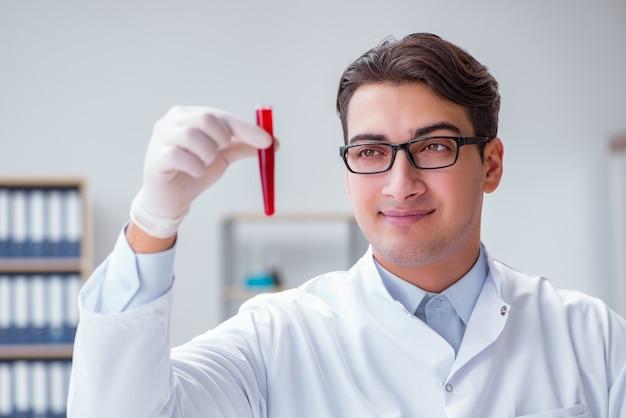 赤いチューブとラボで若い医者