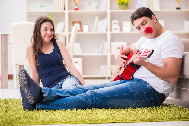 床でギターを弾くロマンチックなペア