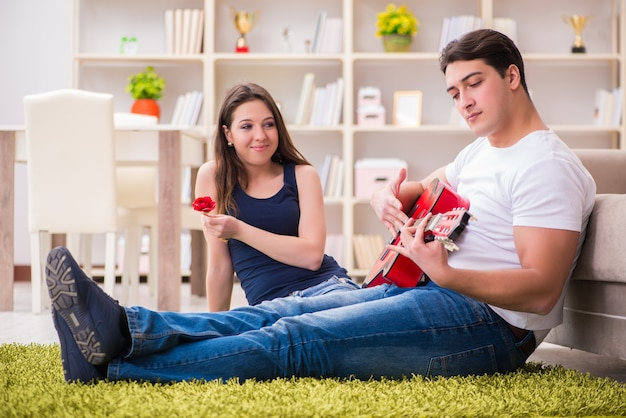 Романтическая пара играет на гитаре на полу