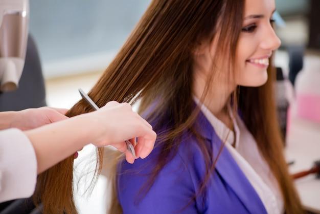 女性は美容室で彼女の髪をやって