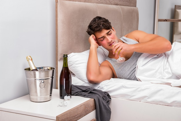 Человек в постели после вечеринки - концепция похмелья