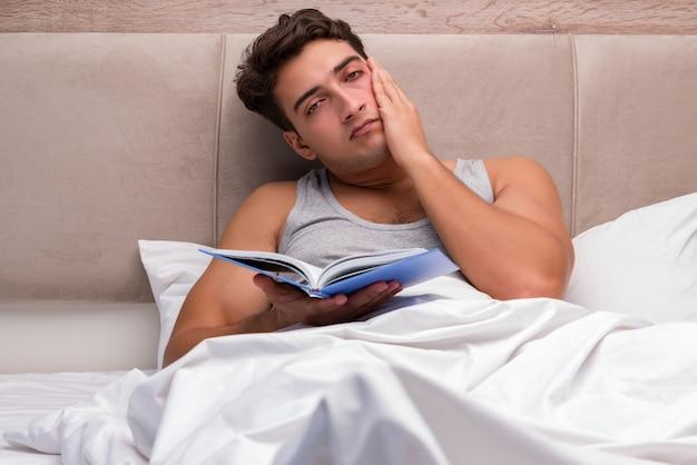 男はベッドで本を読んで
