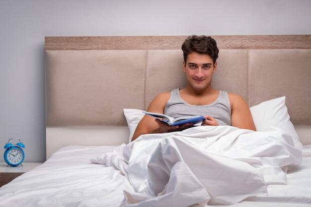Человек читает книгу в постели