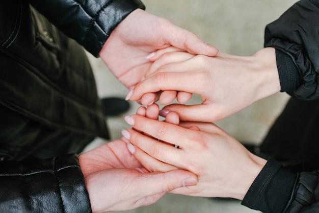 手を繋いでいるカップル。手を見て