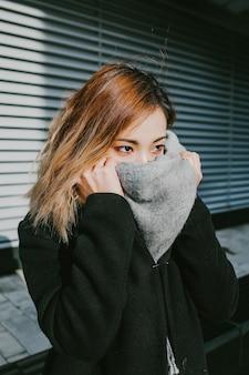 アジアの女の子の外観はスカーフの顔を閉じます