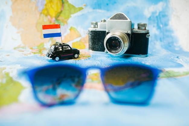 Игрушечный автомобиль и фотоаппарат на фоне карты мира