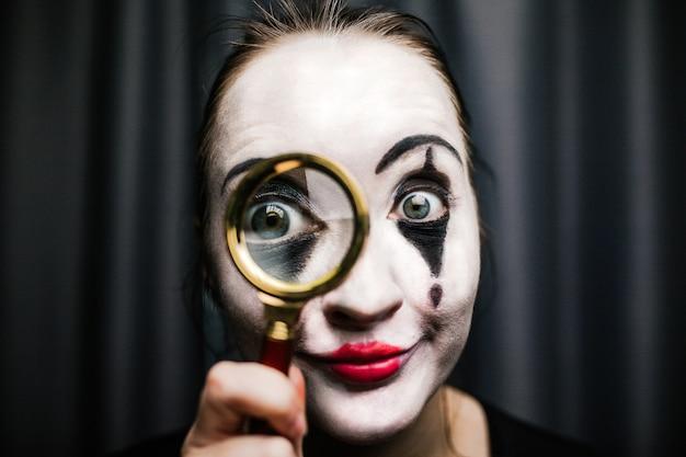 パントマイムをイメージした少女が拡大鏡を持っています。