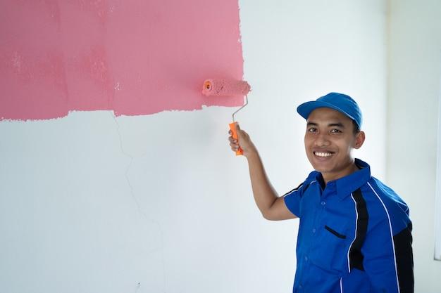Рабочий красит стену в комнате