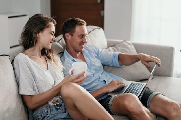 Пара в их доме, используя ноутбук вместе по утрам