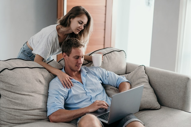 Молодая пара, используя ноутбук вместе, сидя на диване
