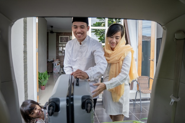 イスラム教徒のアジアのカップルが車のトランクにスーツケースを置く
