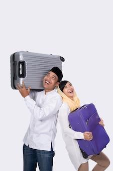 白い背景の上のスーツケースに興奮しているイスラム教徒のカップル