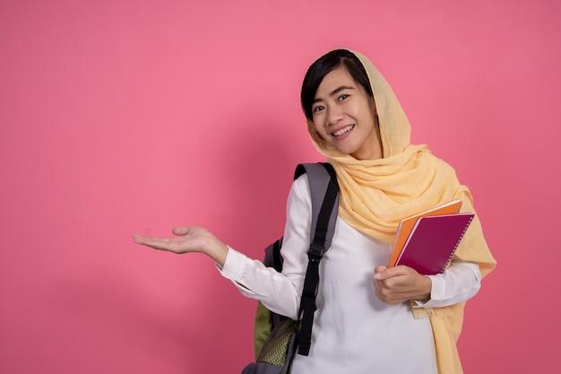 ピンクの背景のイスラム教徒の学生