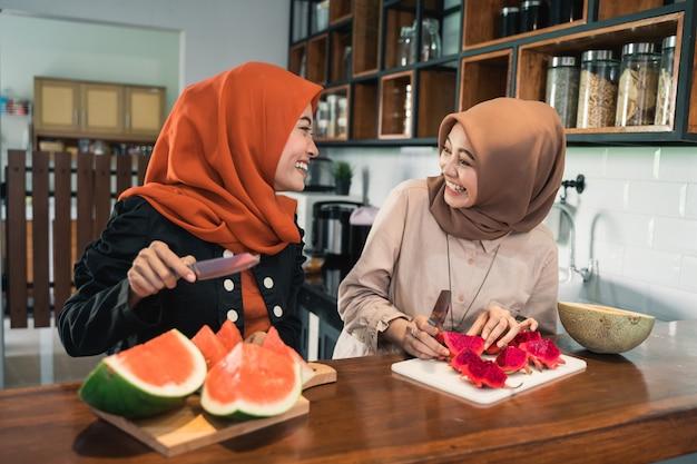 いくつかのフルーツデザートカクテルを準備するイスラム教徒の女性の友人
