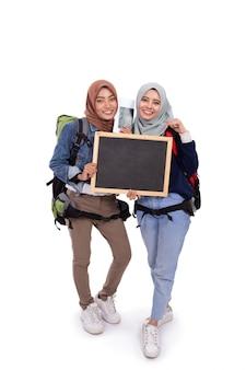 白い背景に分離された笑顔幸せなイスラム教徒のバックパッカー